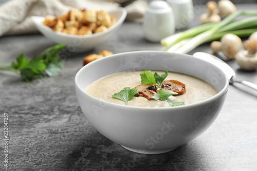 Bowl of fresh homemade mushroom soup on gray table