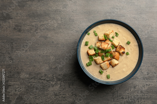 Bowl of fresh homemade mushroom soup on gray background, top view with space for text