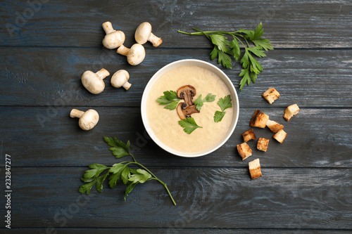 Flat lay composition with bowl of fresh homemade mushroom soup on wooden background