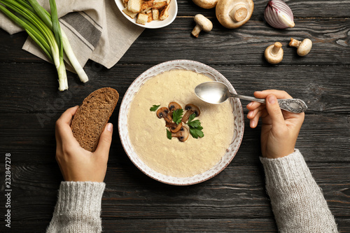 Woman eating fresh homemade mushroom soup from bowl on table, top view