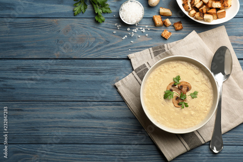 Flat lay composition with bowl of fresh homemade mushroom soup and space for text on wooden background