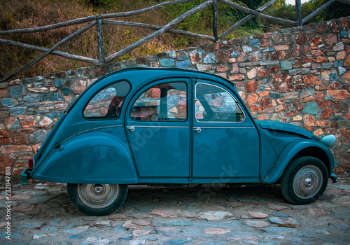 Fotografía  blue retro car on stone wall background