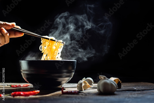 Hand uses chopsticks to pickup tasty noodles with steam and smoke in bowl on wooden background, selective focus Canvas Print
