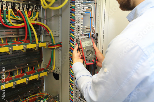 electrician is working in electrical cables distribution fuse box ...  adobe stock