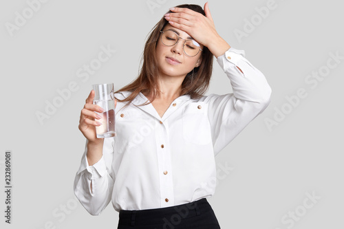 Photo Tired overworked woman keeps hand on forehead, wears transparent glasses, black and white clothes, holds glasses of water, feels thirsty and fatigue, isolated over white background