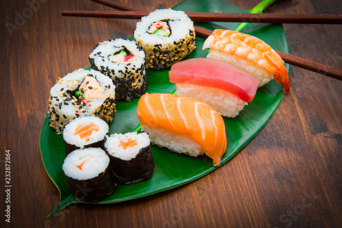 Maki and nigiri sushi set on green leaf  background. Close up