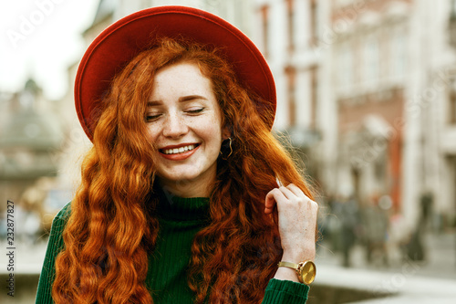 Close up portrait of young beautiful fashionable happy smiling redhead woman with freckles, very long curly hair, wearing green turtleneck, orange hat, golden wrist watch, posing in street Poster Mural XXL