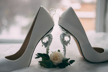 A Pair Of White Wedding Shoes With Rings On A Stool