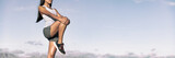 Runner stretching legs hamstring muscles outdoor holding one leg standing outdoor in sky background banner panorama. Running athlete woman doing fitness stretch.