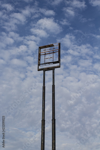 Fotografie, Obraz  Tall empty highway sign frame against a blue sky with clouds, centered, copy spa
