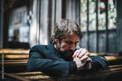 Lonely Christian man praying in the church Fototapet