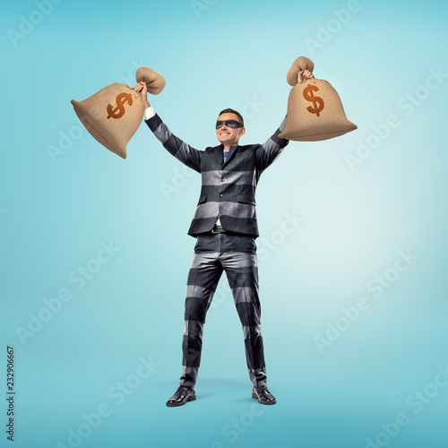 Photo A businessman wearing a classic suit with stripes that resembles a burglar's outfit and a black eye mask stands with his arms up holding two bags of cash