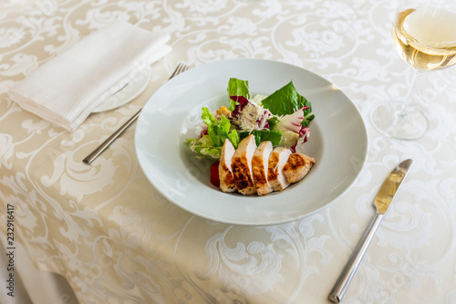 Fotografía  Classic caesar salad with grilled chicken on a white plate