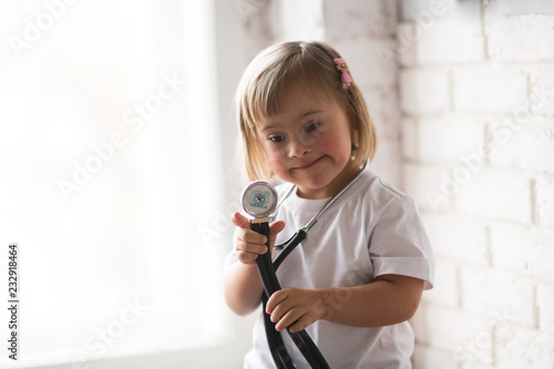 Fotografía  Toddler with Down syndrome plays with stethoscope