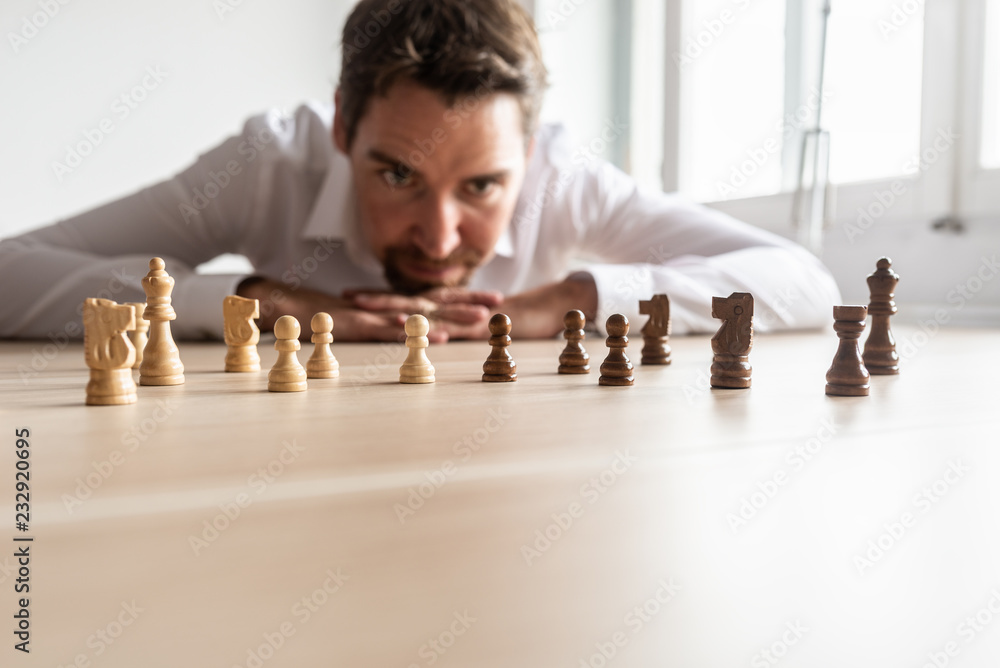 Fotografía Businessman looking at black and white chess pieces on office desk