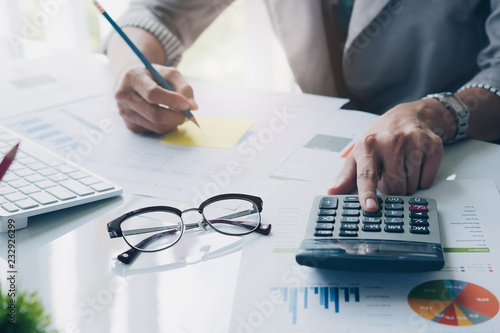 Close up of businessman or accountant hand holding pen working on calculator to Canvas Print