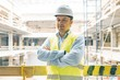 Portrait of male engineer at construction site. Experienced confident builder with arms crossed at a construction site. Building, development, teamwork and people concept