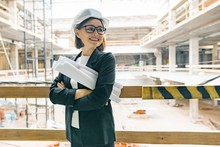 Mature Female Engineer On Construction Site. Building, Development, Teamwork And People Concept