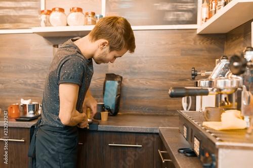 Fototapeta Portrait of young male barista making drinks. Coffee shop business concept obraz na płótnie