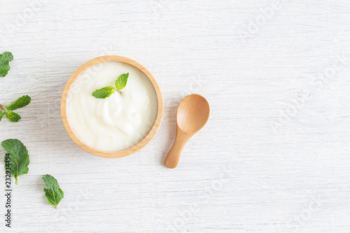 Yogurt in wood bowl on white wooden table Healthy food concept, top view and copy space