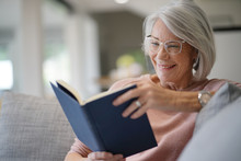Senior Woman Reading On Couch...
