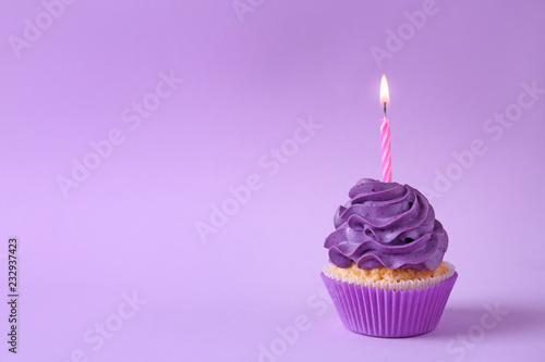 Tasty cupcake with burning candle on color background Wallpaper Mural