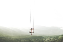 Surreal Moment Of A Woman Having Fun On A Swing Hanging From The Sky