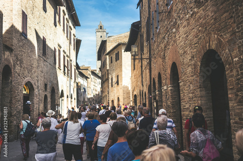 Crowd of tourists people walk together stretched and with the street full in San Gimignano near Siena in Tuscany, Italy. Vacation and culutre in a medieval city full of history