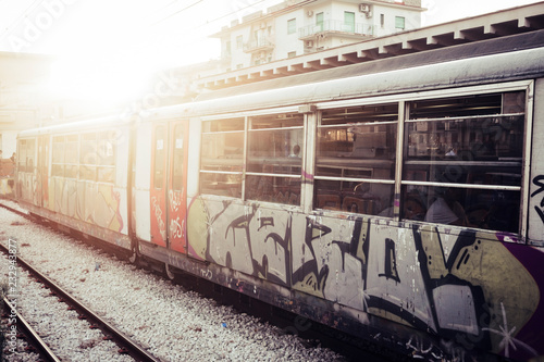 A train with closed doors waiting for passengers at the railway station. Street art and urban culture painted on the tube, Sunlight in background - 232943877