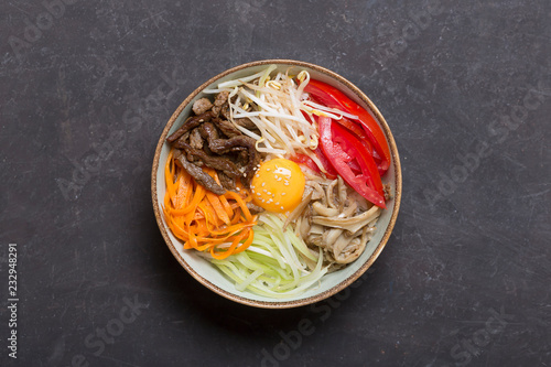 Traditional Asian Bibimbap dish with rice and vegetables on dark background. Central composition