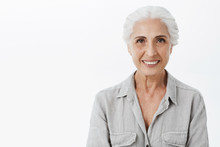 Waist-up Shot Of Cute And Kind Wise Elderly Woman With White Hair In Casual Shirt Smiling Broadly With Assured And Delighted Look Being Amused And Charismatic Posing Against Gray Background
