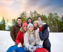 Friendship, Technology And People Concept - Group Of Smiling Teenage Friends With Snow Tubes Taking Picture By Smartphone Selfie Stick Outdoors In Winter Over Natural Background