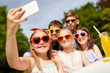 holidays, childhood and technology concept - happy kids in sunglasses taking selfie on birthday party at summer garden
