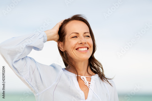Photographie  people and leisure concept - happy smiling woman on summer beach