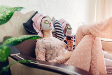 Mother And Her Adult Daughter Applied Facial Masks And Cucumbers On Eyes. Women Chilling While Having Wine