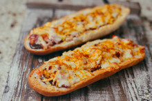 A Couple Of Traditional French Split Baguettes With Cheese And Other Complex Filling. On Wooden Retro Background Stand Tray.