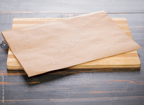 cutting board and parchment lay on a dark wooden tabletop