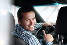 Modern Man Sitting In A Car And Showing His Thumb Up.