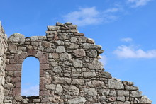 Window Opening In Old Stone Wall Against Blue  Sky