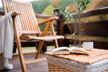 A Wooden Chair And A Book On A Basket On A Terrace On A Sunny Day In Autumn.