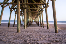 Myrtle Beach South Carolina. Looking Under A Long Wooden Pier Along The Wide Sandy Beaches Of The Grand Strand On The Atlantic Ocean Coast Of South Carolina.