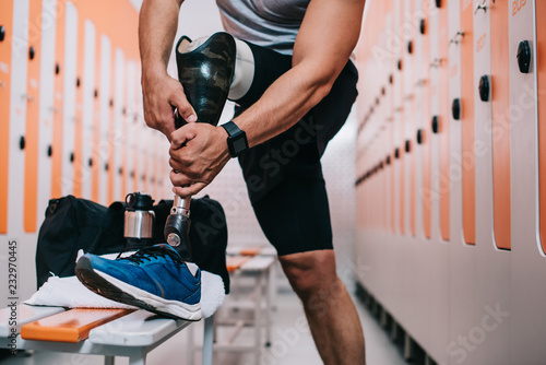 Fotografie, Obraz  cropped shot of sportsman putting on artificial leg at gym changing room