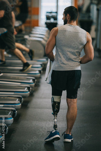rear view of athletic sportsman with artificial leg walking by gym Canvas Print
