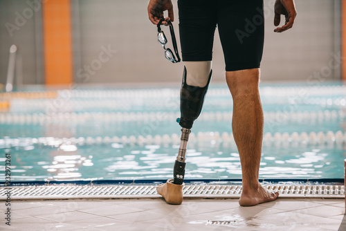 Photo cropped shot of swimmer with artificial leg standing in front of indoor swimming