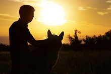 Silhouette Of A Man And A Dog Watching The Sun Set On The Horizon In A Field, Boy Fondle His Pet On Nature, Concept Of Emotional Health