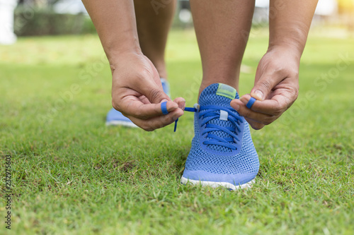 Fotografía  Young woman runner tying shoelaces in lawn outdoors.