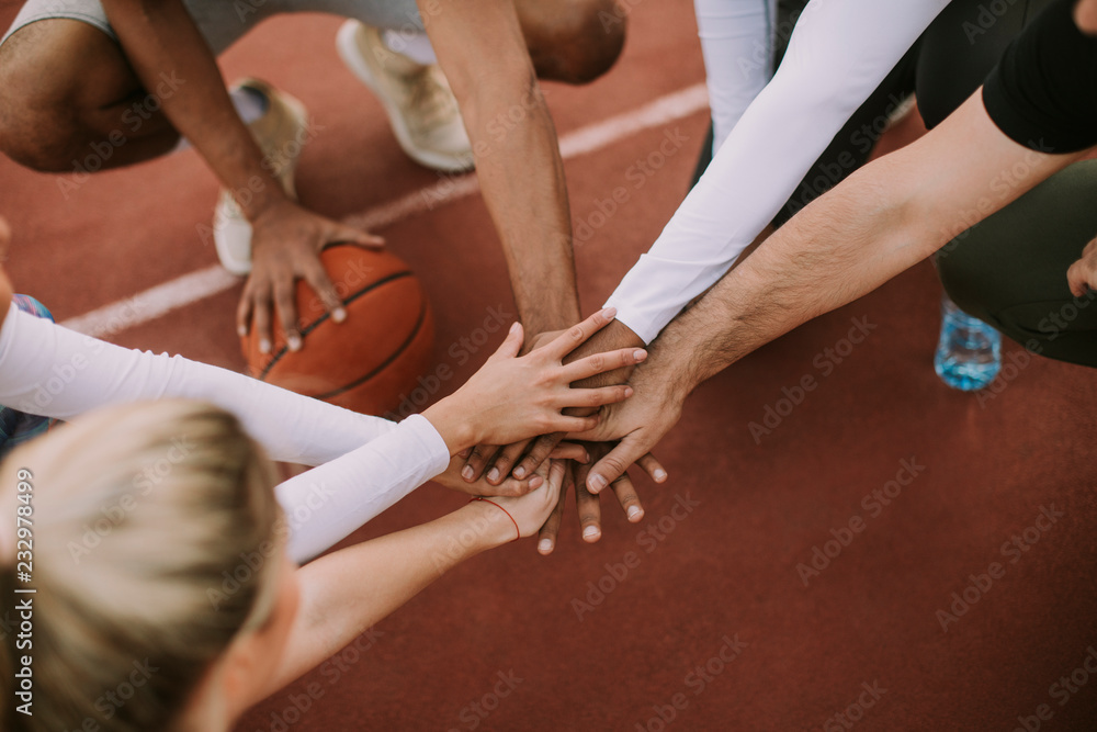 Fototapety, obrazy: Top view of basketball team holding hands over court