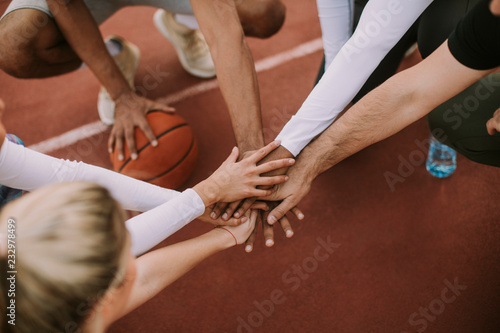 Fototapeta Top view of basketball team holding hands over court obraz