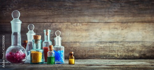 Poster Pharmacie Vintage medications in small bottles on wood desk. Old medical, chemistry and pharmacy history concept background. Retro style.