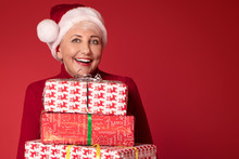 Smiling Mature Woman In Red Santa Claus Hat With Gifts.